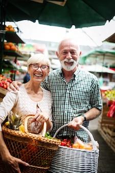 Portret van mooi bejaard echtpaar op de markt die voedsel koopt