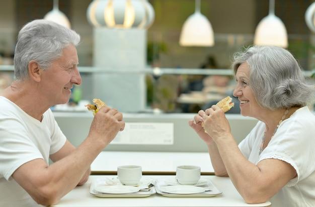 Portret van mooi bejaarde echtpaar dat fastfood eet