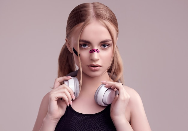 Portret van mooi blond meisje met glamourpleisters op haar gezicht luisteren muziek in witte hoofdtelefoons bij studio