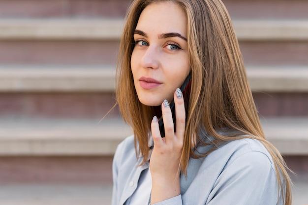 Portret van mooi blondemeisje die op telefoon spreken