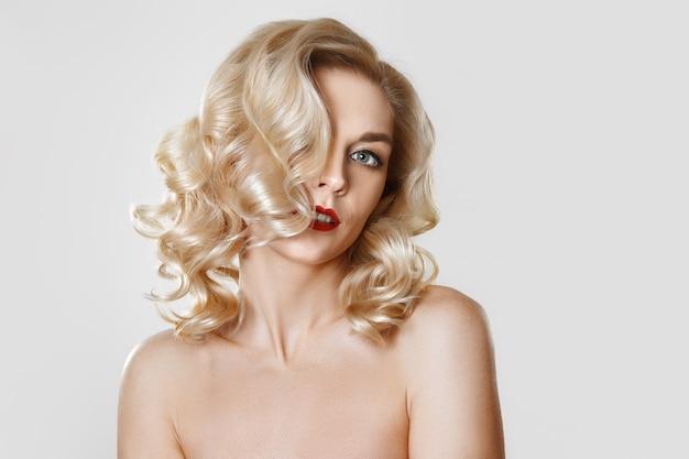 Portret van mooi blondemeisje met krullend haar, de samenstelling van het kattenoog, rode lippen. concept mock up foto.