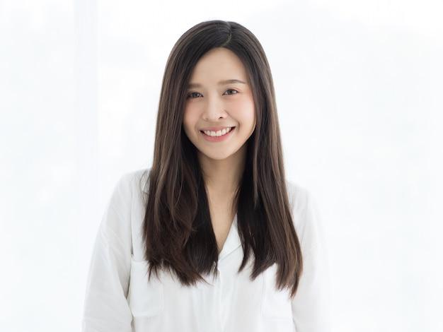 Portret van mooi en schattig lang haar aziatische vrouw met een wilde en warme glimlach op haar gezicht.