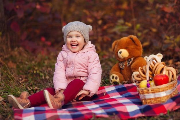 Portret van mooi gelukkig kind zittend op plaid met herfst kleurrijke bladeren achtergrond. picknickmand met appels en bagels, speelgoedberen. grappig meisje buiten in herfstpark.