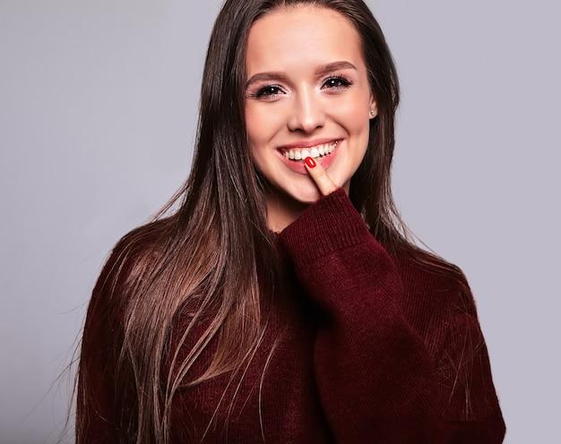 Portret van mooi gelukkig leuk donkerbruin vrouwenmodel in toevallige warme rode die sweaterkleren op grijs met avondmake-up en kleurrijke lippen wordt geïsoleerd