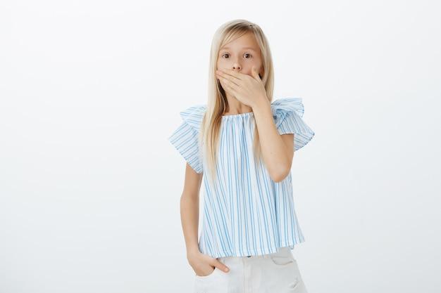 Portret van mooi geschokt meisje met blond haar in blauwe blouse, hijgend, mond bedekt om niet te schreeuwen van angst, verbaasd en doodsbang met enge spin, staande tegen grijze muur