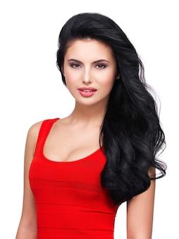 Portret van mooi gezicht van een jonge glimlachende vrouw met lang bruin haar in rode kleding