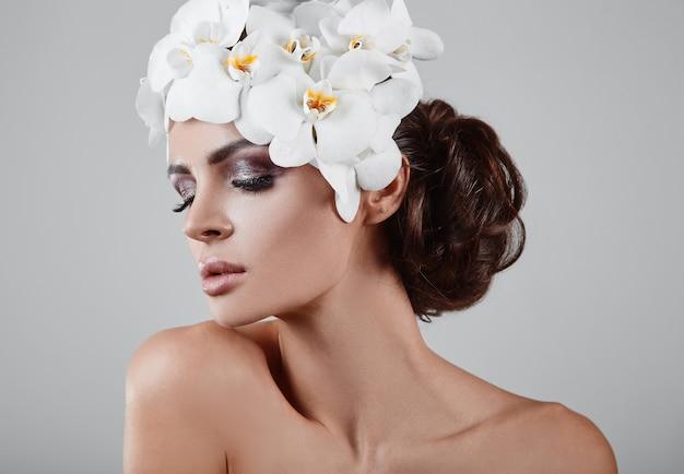 Portret van mooi, glamoureus, sensueel donkerbruin model met bloemen