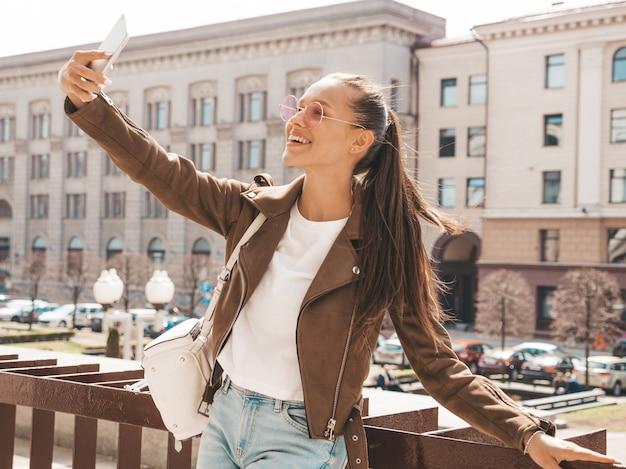 Portret van mooi glimlachend donkerbruin meisje in de zomer hipster jasje. model nemen selfie op smartphone.