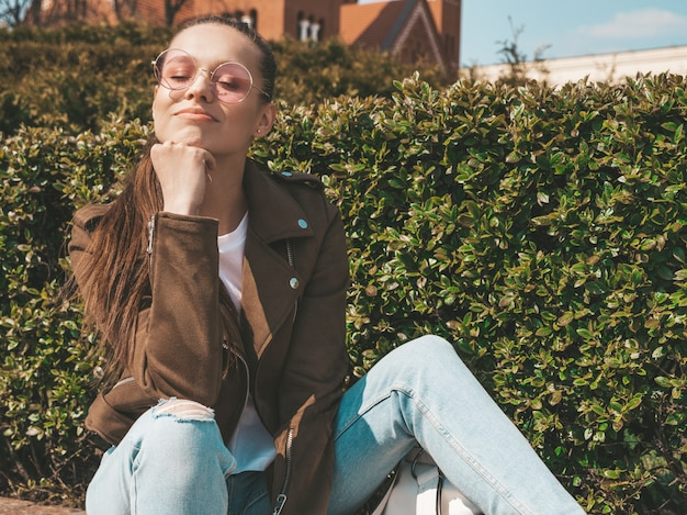 Portret van mooi glimlachend donkerbruin model gekleed in de zomer hipster jas en jeans kleding trendy meisje zittend op de bank in de straat