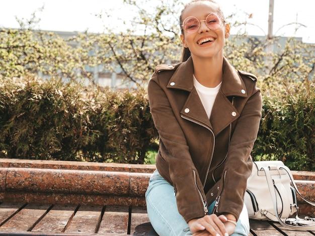 Portret van mooi glimlachend donkerbruin model gekleed in de zomer hipster jas en jeans kleding trendy meisje zittend op het bankje in de straat grappige en positieve vrouw in zonnebril