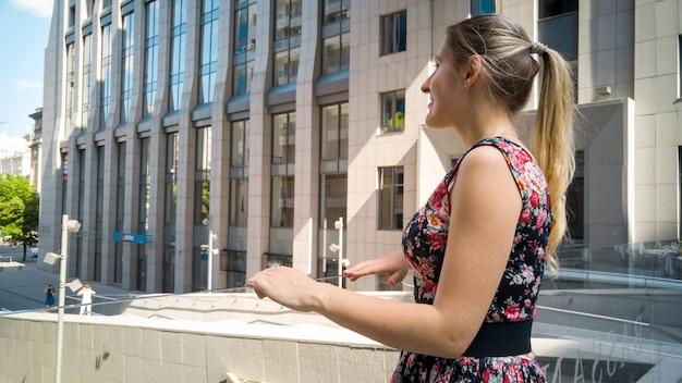 Portret van mooi glimlachend jong meisje met lang haar dat op straat van moderne stad kijkt