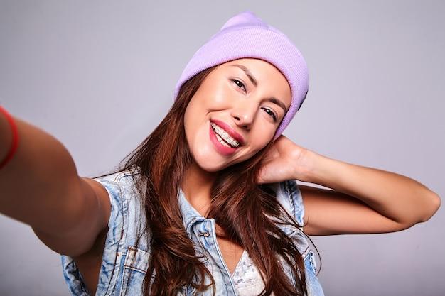 Portret van mooi glimlachend leuk donkerbruin vrouwenmodel in de toevallige kleren van de zomerjeans zonder make-up in purpere beanie die selfie foto op telefoon maken die op grijs wordt geïsoleerd