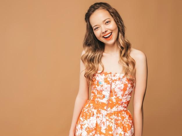 Portret van mooi glimlachend leuk model met roze lippen. meisje in zomer kleurrijke jurk. model poseren