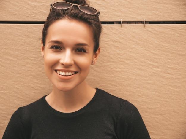 Portret van mooi glimlachend model gekleed in de zomerkleren. trendy meisje poseren in de straat. grappige en positieve vrouw die pret heeft
