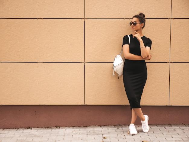 Portret van mooi glimlachend model gekleed in de zomerkleren. trendy meisje poseren in de straat. grappige en positieve vrouw die pret in zonnebril hebben