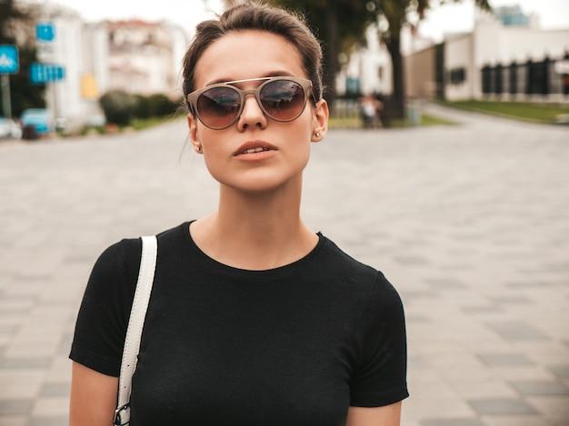 Portret van mooi glimlachend model gekleed in de zomerkleren. trendy meisje poseren in de straat in zonnebril. grappige en positieve vrouw die pret heeft