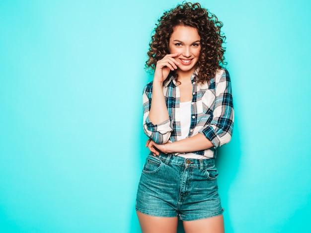 Portret van mooi glimlachend model met afro krullen kapsel gekleed in de zomer hipster kleding. trendy grappige en positieve vrouw