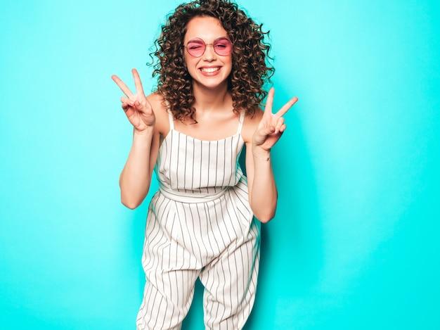 Portret van mooi glimlachend model met afro krullen kapsel gekleed in zomer hipster kleding. sexy zorgeloos meisje poseren in de buurt van blauwe muur. trendy grappige en positieve vrouw