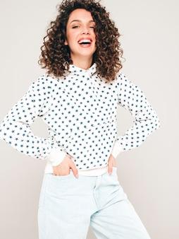 Portret van mooi glimlachend model met afro krullen kapsel gekleed in zomer hipster kleding. sexy zorgeloos meisje poseren in studio op grijze achtergrond. trendy grappige en positieve vrouw