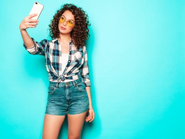 Portret van mooi glimlachend model met afro krullen kapsel gekleed in zomer hipster kleding. sexy zorgeloos meisje poseren in studio op grijze achtergrond. trendy grappige vrouw neemt selfie foto