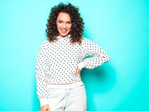 Portret van mooi glimlachend model met afro krullen kapsel gekleed in zomer hipster kleding. trendy grappige en positieve vrouw in witte hoodie