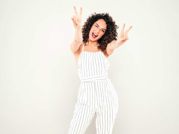 Portret van mooi glimlachend model met afro krullen kapsel gekleed in zomer hipster kleding. trendy grappige en positieve vrouw vertoont vredesteken