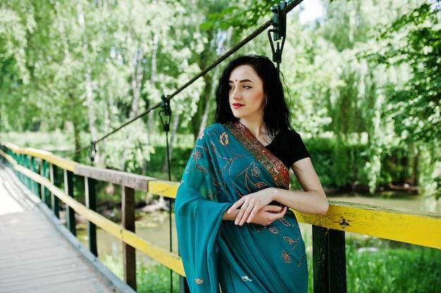 Portret van mooi indisch brumettemeisje of hindoes vrouwenmodel op brug. traditionele indiase choli van kostuumlehenga.