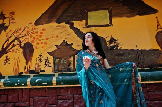 Portret van mooi indisch brumettemeisje of hindoes vrouwenmodel tegen japanse grafitimuur.