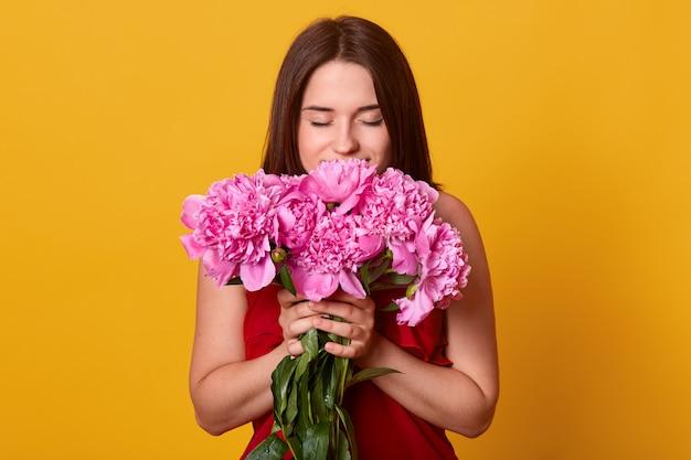Portret van mooi jong donkerbruin meisje die boeket van roze pioenen houden tegen gele studiomuur, die kleding draagt, bloemen ruikt