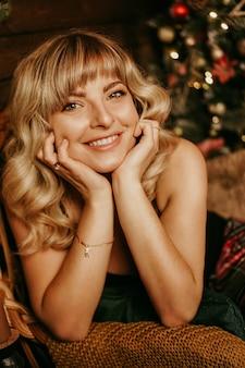 Portret van mooi jong meisje met lang krullend haar op een kerst achtergrond met verlichting close-up magische warme nieuwe jaar foto gezellig interieur