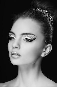 Portret van mooi jong meisje met maniersamenstelling dat op zwarte wordt geïsoleerd