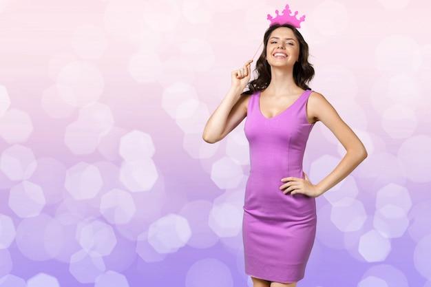 Portret van mooi jong meisje met papieren feestelijke kroon