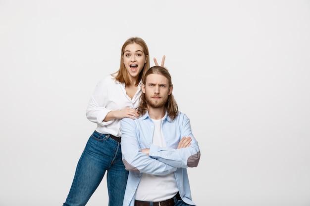 Portret van mooi jong paar die vrede of overwinningsteken tonen op witte studioachtergrond