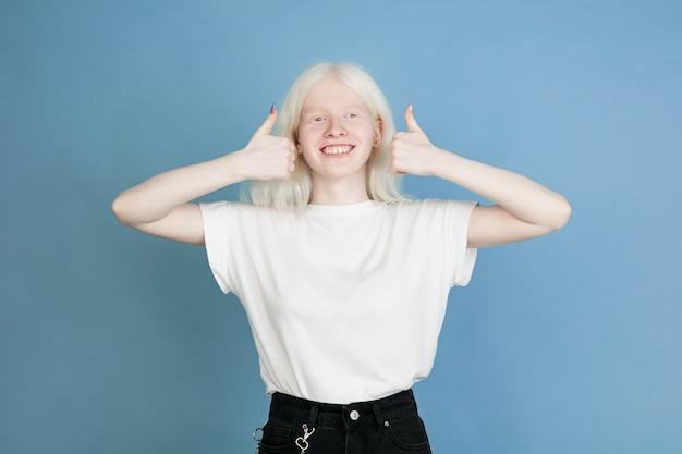 Portret van mooi kaukasisch albinomeisje dat op blauwe muur wordt geïsoleerd