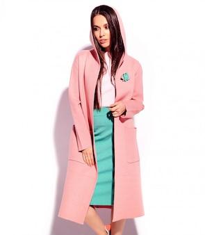 Portret van mooi kaukasisch het glimlachen donkerbruin vrouwenmodel in heldere roze overjas en de zomer modieuze blauwe die rok op witte achtergrond wordt geïsoleerd