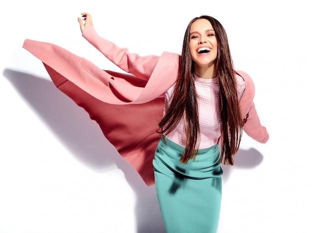 Portret van mooi kaukasisch het glimlachen donkerbruin vrouwenmodel in heldere roze overjas en de zomer modieuze blauwe rok