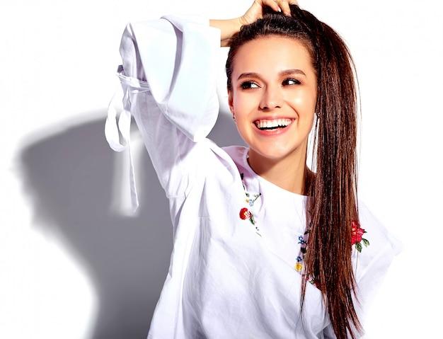 Portret van mooi kaukasisch het glimlachen donkerbruin vrouwenmodel in witte blouse en de zomer modieuze jeans met bloemendruk