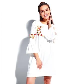 Portret van mooi kaukasisch het glimlachen donkerbruin vrouwenmodel in witte de zomer modieuze kleding dat op witte achtergrond wordt geïsoleerd