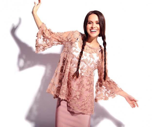 Portret van mooi kaukasisch het glimlachen donkerbruin vrouwenmodel met dubbele vlechten in heldere roze de zomer modieuze die kleren op witte achtergrond worden geïsoleerd.