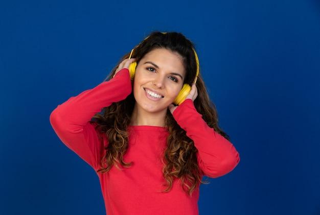 Portret van mooi kaukasisch meisje met krullend haar en koptelefoon luisteren muziek geïsoleerd op een witte muur