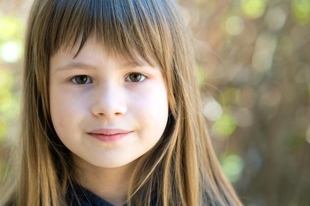 Portret van mooi kindmeisje met grijze ogen en lang blond haar buitenshuis op een wazige, lichte achtergrond. schattige vrouwelijke jongen op warme zomerdag buiten.
