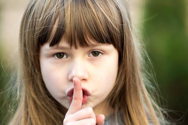 Portret van mooi kindmeisje met grijze ogen en lang blond haar die puntvinger op haar lippen met stilzucht houden