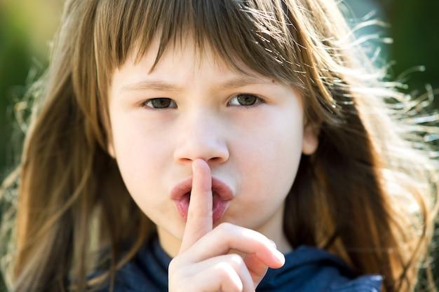 Portret van mooi kindmeisje met grijze ogen en lang haar die puntvinger op haar lippen met stilte zucht houden