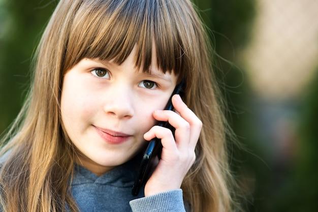 Portret van mooi kindmeisje met lang haar dat op celtelefoon spreekt. kleine vrouwelijke jongen communiceren via smartphone. kinderen communicatieconcept.