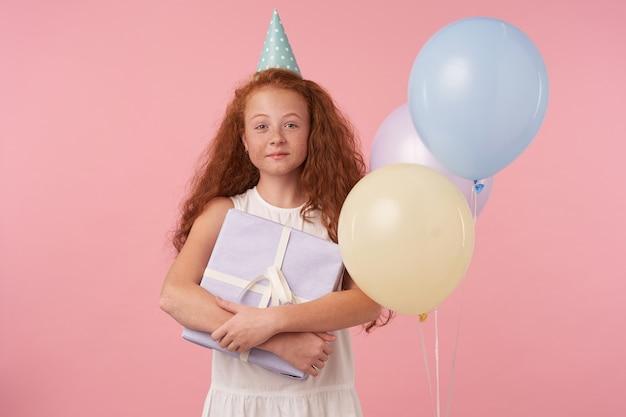 Portret van mooi klein krullend meisje met lang foxy haar staande op roze in witte elegante jurk met oprechte charmante glimlach, in hoge geest