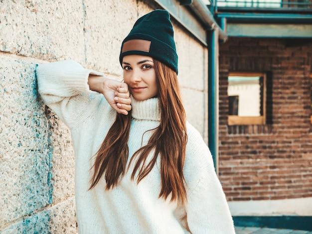 Portret van mooi lachend model. vrouw gekleed in warme hipster witte trui en muts. trendy meisje poseren in de buurt van muur in de straat
