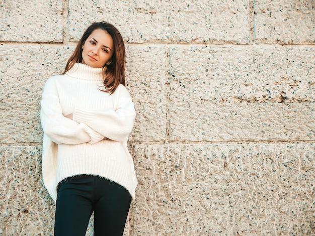 Portret van mooi lachend model. vrouw gekleed in warme hipster witte trui. poseren bij de muur op straat