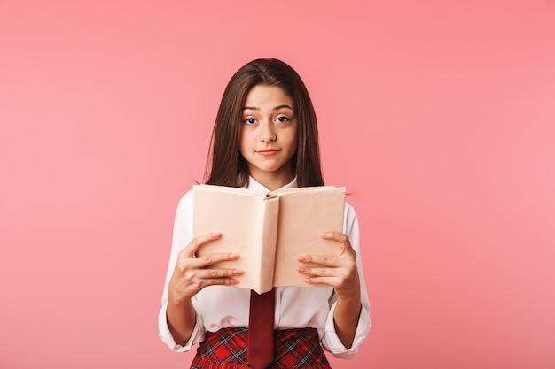 Portret van mooi meisje 15-16j in schooluniform leesboek, terwijl status geïsoleerd over rode muur