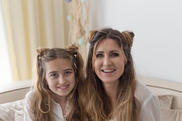 Portret van mooi meisje bij woonkamer met haar moederzitting en het glimlachen in wit overhemd