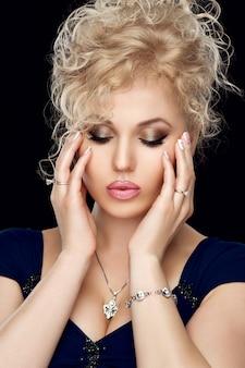 Portret van mooi meisje blonde met gouden avond make-up, volle lippen, french manicure, nette nagels. schitterende sieraden, zilveren hanger, ring, armband.